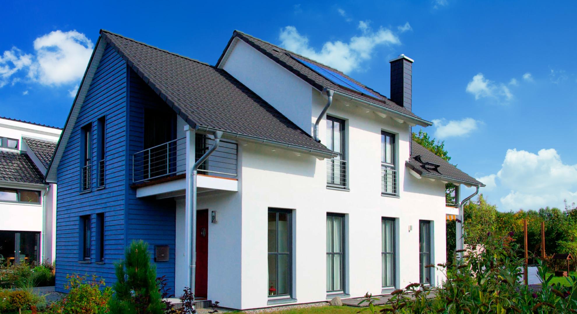 TD-Talot: Yksilöllistä talorakentamista yli 30 vuoden kokemuksella. Kuvassa valkoinen omakotitalo kesällä, pihalla vehreitä pensaita.